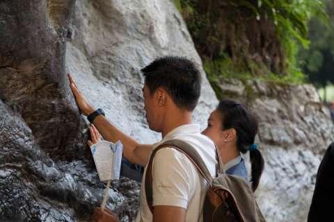 les pèlerins effleurent de la main la paroi de la grotte